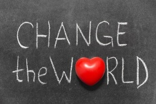 change the world phrase handwritten on blackboard with heart symbol instead of O