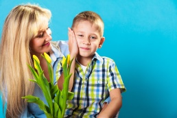 Boy celebrating mother's day. little child lad giving flowers yellow tulips to his mom mother studio shot on blue