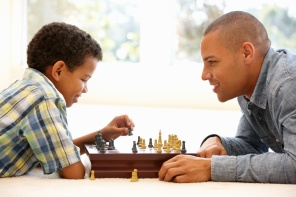 Father playing chess with son