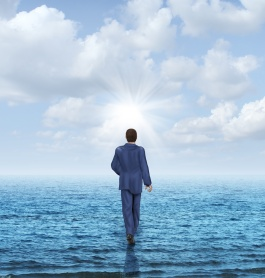 Walk on water with a businessman walking on the surface of an ocean as a business concept of confidence and courage to take on an impossible challenge and achieve success with the power of belief.