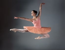 Beautiful female ballet dancer on a grey background. Ballerina is wearing an orange tutu, pink stockings and pointe shoes.
