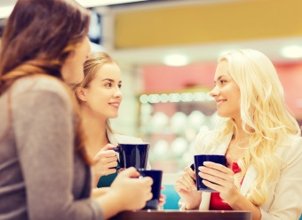 drinks, communication, friendship and people concept - happy young women with cups sitting at table and talking in mall or cafe