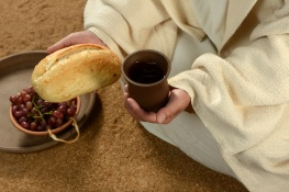 Jesus hands holding bread and wine with tray of grapes in background