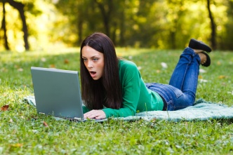 Surprised woman using laptop in park