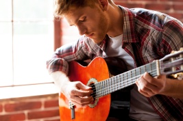 Handsome man playing guitar. Close-up of young man playing acoustic guitar while sitting in front of the window