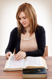 Young christian woman turning pages of the Bible searching for promises