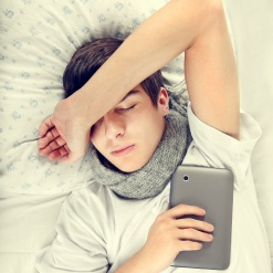 Toned Photo of Tired Young Man sleep with Tablet Computer on the Bed