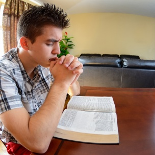 Teenager having daily devotional at home. Christian lifestyle. Peace and love while praying