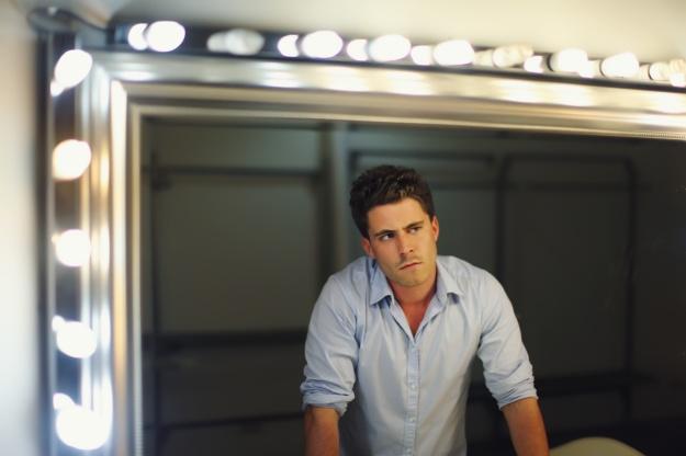 Homme en pleine reflexion devant le miroir