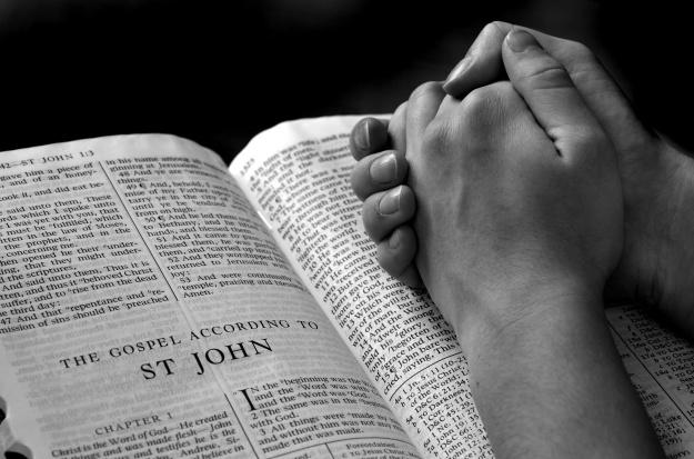 HANDS PRAYING ON BIBLE.012615.jpg